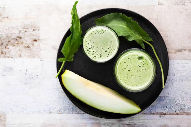 jus de melon, cantaloup avec smoothie de fusée de jardin, smoothie vert, detox - cold pressed photos et images de collection