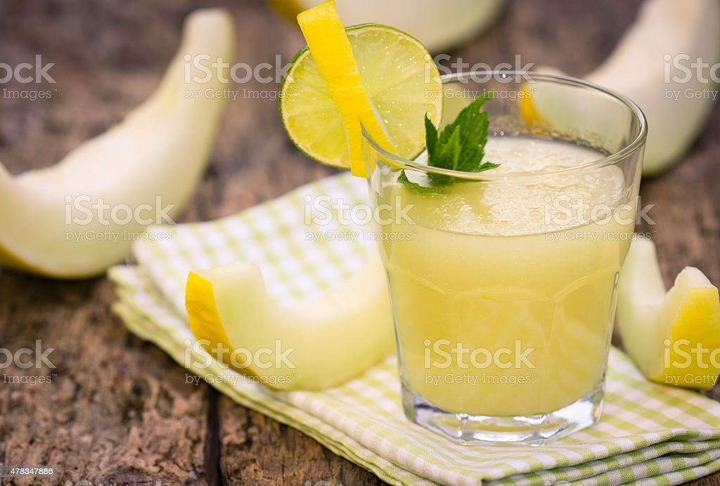Melon juice in the glass on the wooden table stock photo