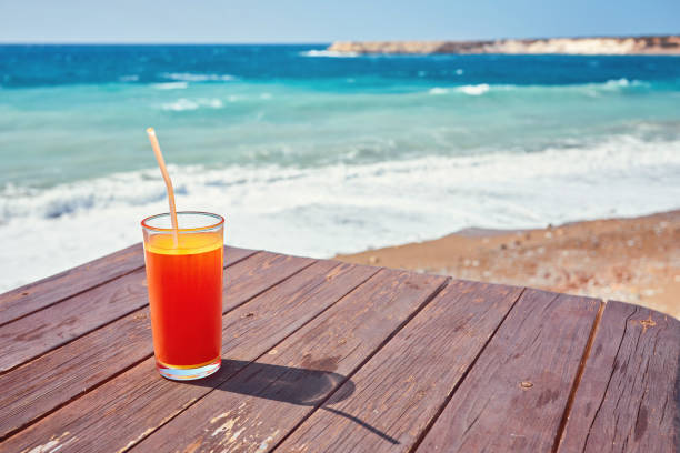 Melon juice on a sea beach. Glasses with red drink and straw stands on a fallen coconut stock photo