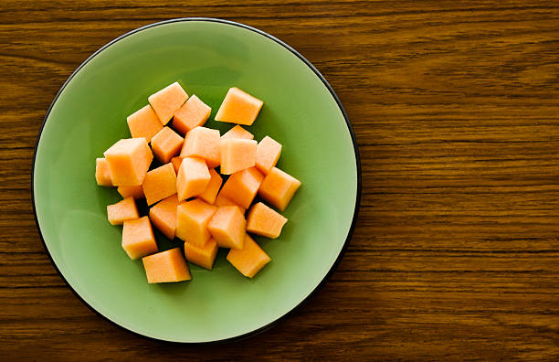 Melon on a glazed plate with textured timber background.