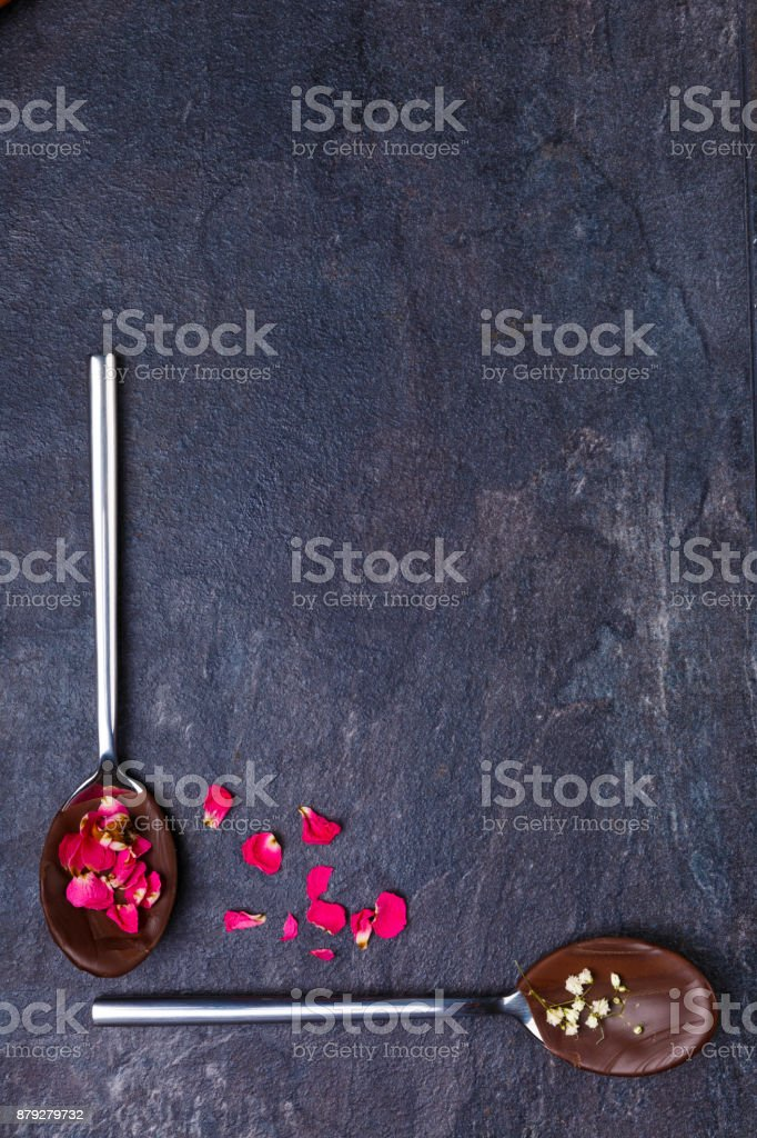 Melted and frozen chocolate on spoons on a stone background. stock photo