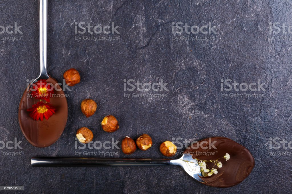 Melted and frozen chocolate on spoons with hazelnut next to a stone background close-up. stock photo