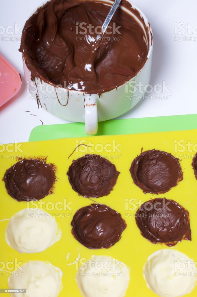 Melted black chocolate in white cups. Nearby silicone mold smeared...