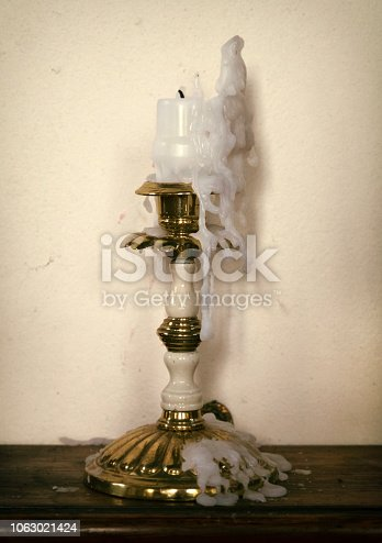 An old-fashioned style candlestick containing a candle stub; both are covered with drips of melted wax. (Vintage colouring.)