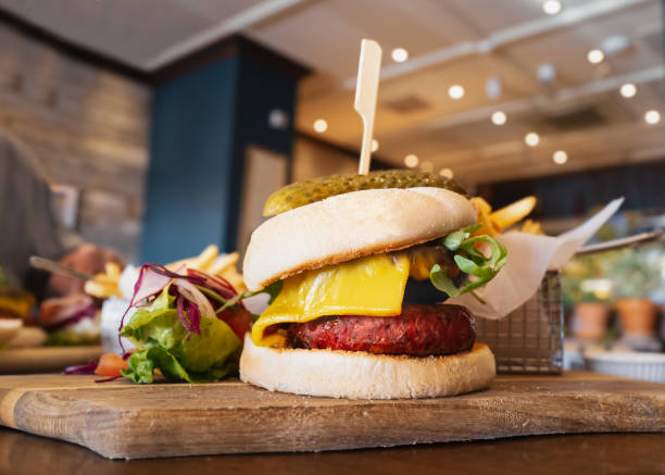 Melted cheese on a portobello mushroom and beetroot and bean vegetarian burger in a bun, on a wooden serving board, with a side salad and metal basket of fries. A wooden skewer and gherkin are on top. stock photo