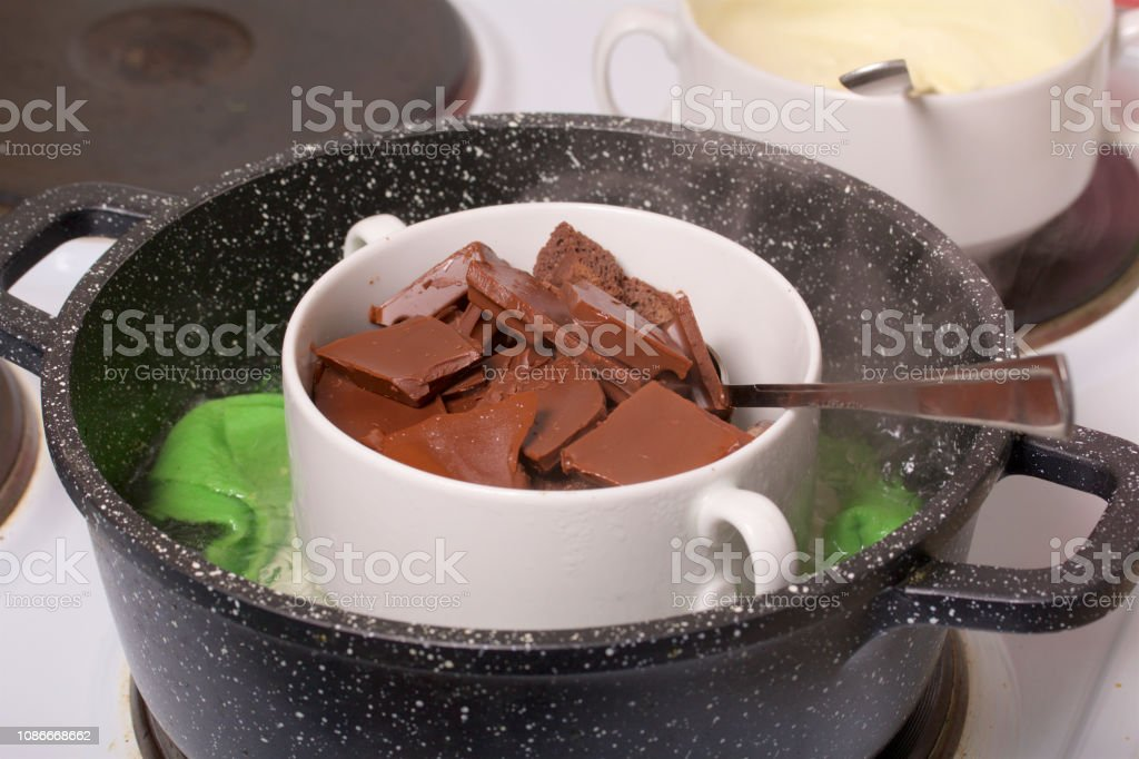 Melted white and black chocolate in the water bath. Stand for making...