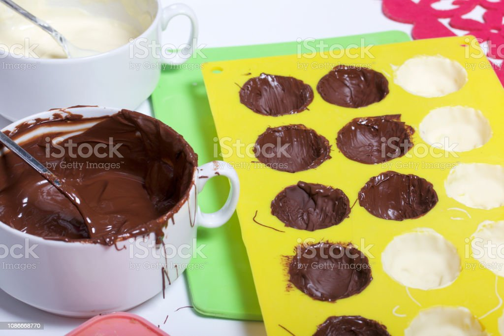 Melted white and black chocolate in white cups. Nearby silicone mold...