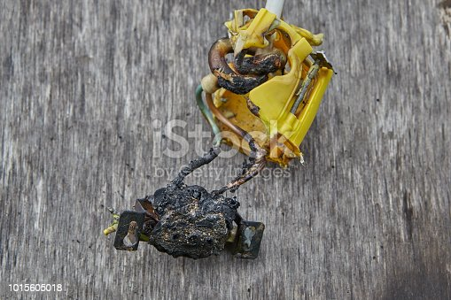 istock Melted-off and burned plastic socket of power supply. 1015605018