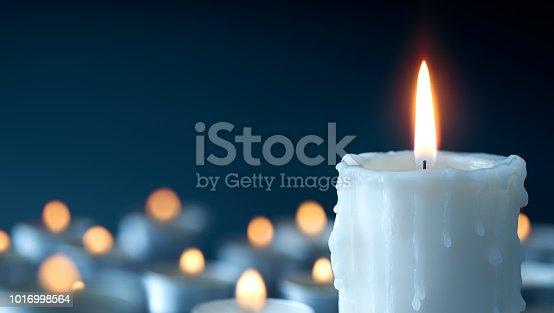 istock Melting candle on cool blue background 1016998564