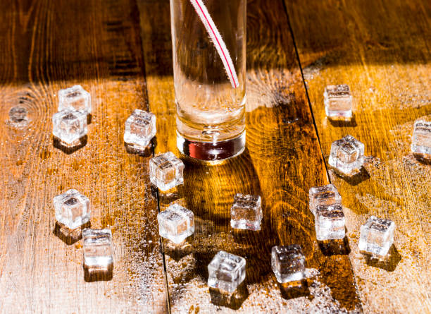 Melting cubes of transparent cold ice and a glass of soda with cocktail straw stock photo