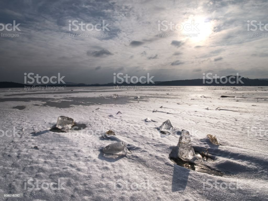 Melting ice crystals and icebergs. The beach covered by thick ice stock photo
