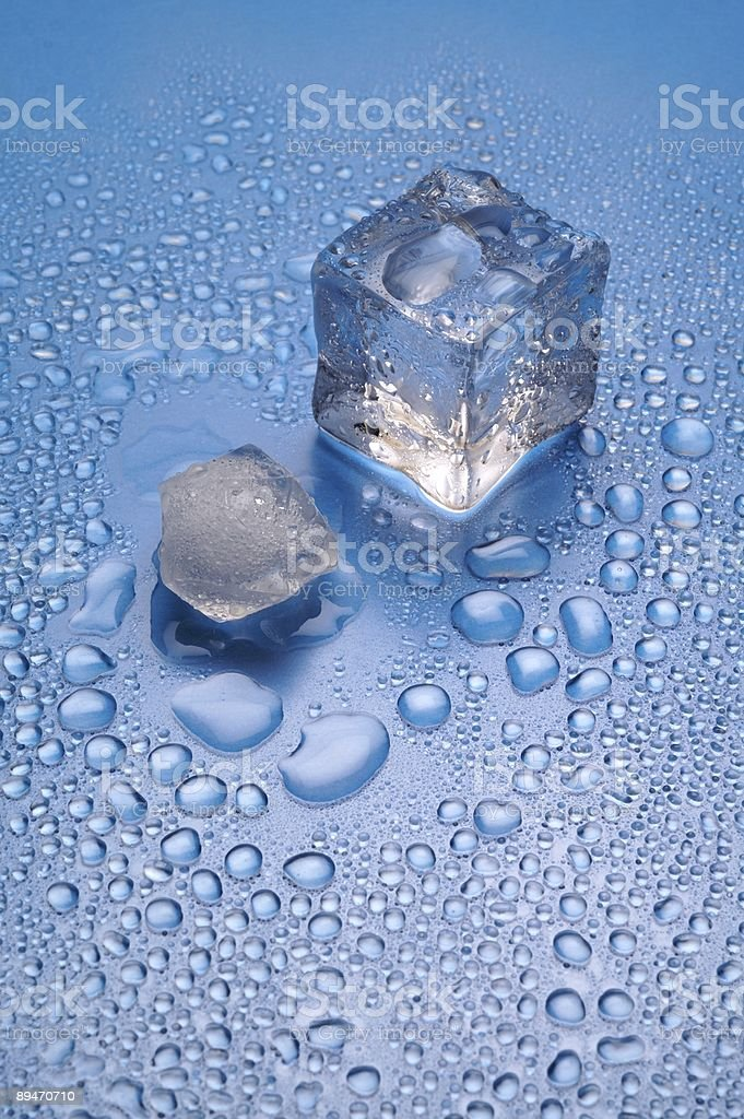 Melting ice on blue background vertical (1) royalty-free stock photo