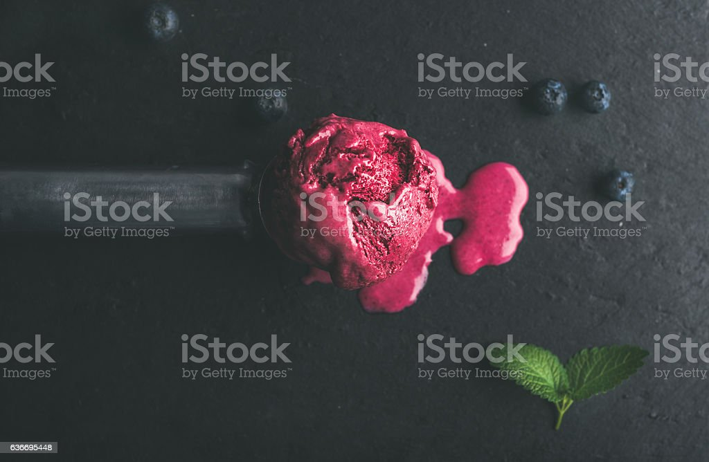 Melting scoop of blueberry ice-cream over black slate stone - Photo