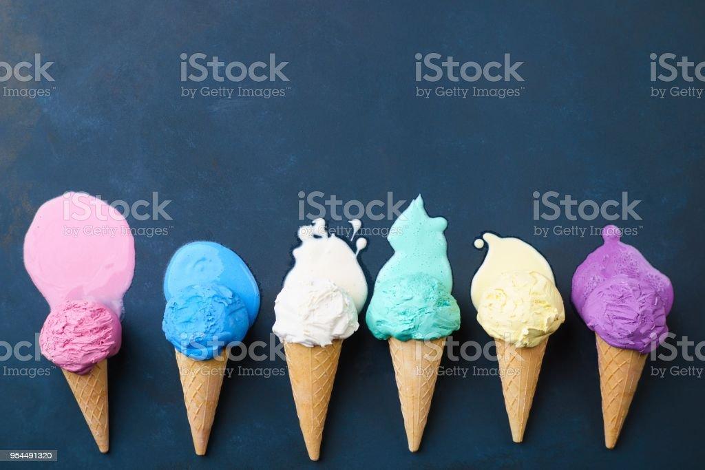 Melting various ice cream  cones, dark background stock photo