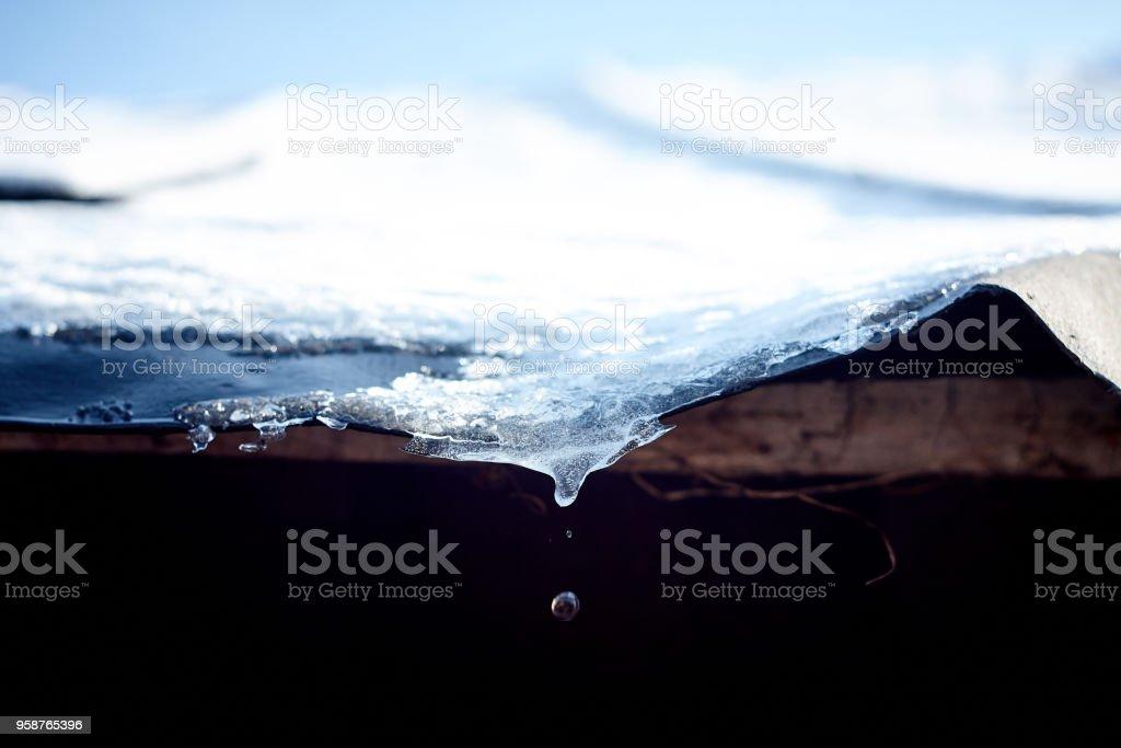 コントラストで雪に覆われた屋根の上の溶解水ドロップ - まぶしいのロイヤリティフリーストックフォト