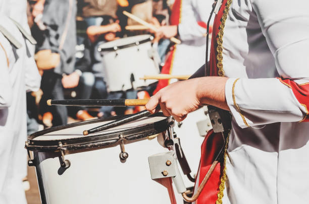 Member of a military fanfare playing a mobile bass drum on a parade. Member of a military fanfare playing a mobile bass drum. Playing a mobile bass drum with drumsticks. Bass drum attached to the body, musician walking and playing on a parade. nicoya peninsula stock pictures, royalty-free photos & images