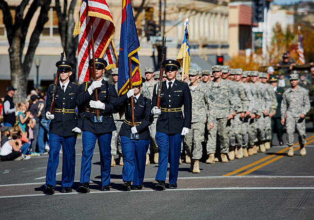 ROTC Members marching in Veterans Day Parade Prescott, Arizona, United States - November 11, 2016: ROTC members marching together holding flags in Veterans day Parade military parade stock pictures, royalty-free photos & images