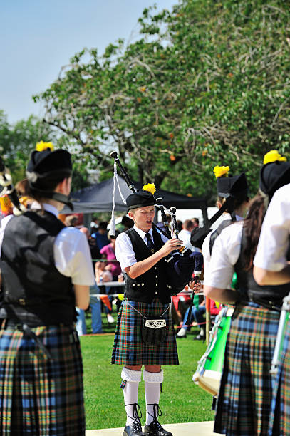 Members of a Scottish pipe band performing outdoors Castle Douglas, Scotland - July 30, 2011: Members of Kirkcudbright and District Pipe Band providing entertainment in Carlingwark Park as part of the towns Douglas Day celebrations. The young piper is squinting due to the bright sunshine johnfscott stock pictures, royalty-free photos & images