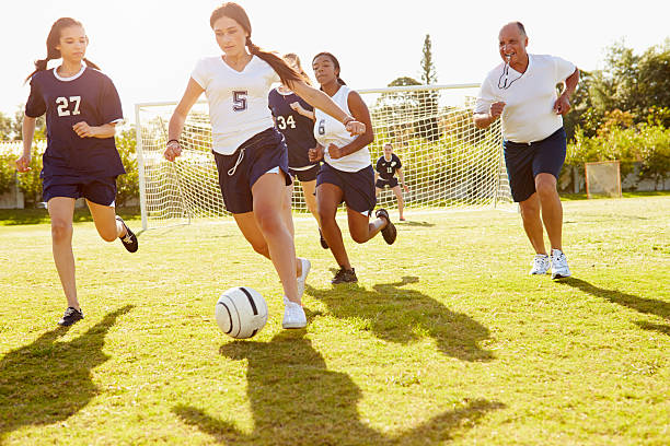 Members Of Female High School Soccer Playing Match Members Of Female High School Soccer Playing Match female high school student stock pictures, royalty-free photos & images