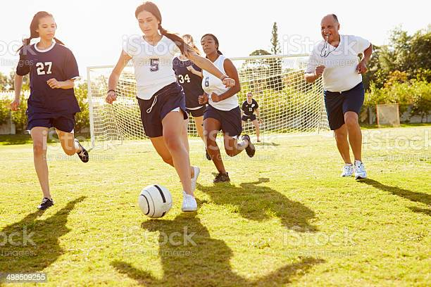 Members Of Female High School Soccer Playing Match Stock Photo - Download Image Now