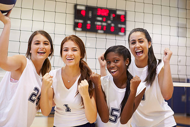 members of female high school volleyball team - volleyball sport stock photos and pictures