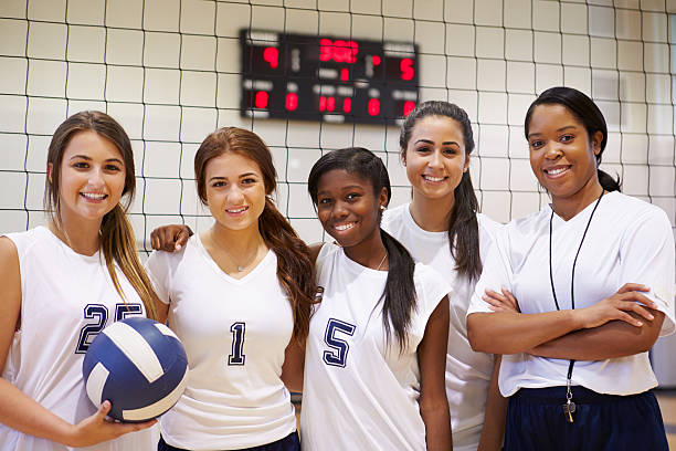 Members Of Female High School Volleyball Team With Coach Members Of Female High School Volleyball Team With Coach Smiling To Camera female high school student stock pictures, royalty-free photos & images