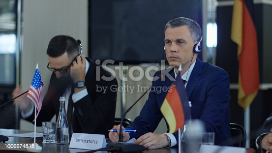 609903512 istock photo Members of international summit in headphones 1006674818