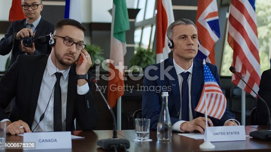 609903512 istock photo Members of international summit in headphones 1006678326