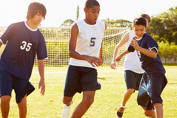 members of male high school soccer playing match - high school sports stock pictures, royalty-free photos & images