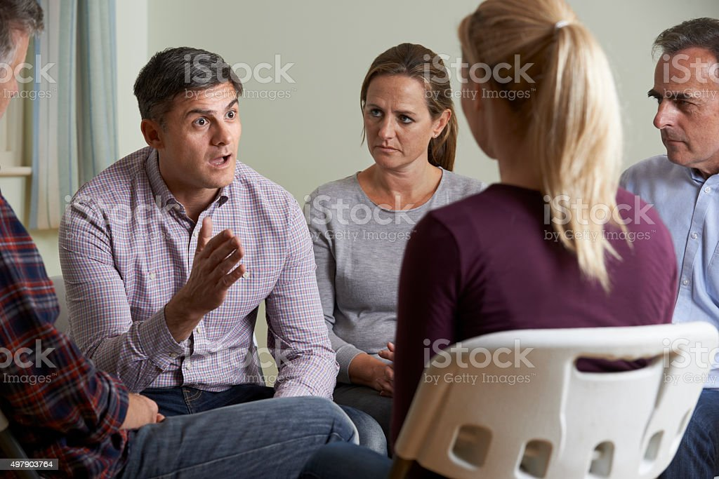 Members Of Support Group Sitting In Chairs Having Meeting stock photo