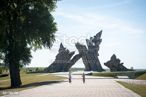 Kaunas, Lithuania - August 15, 2015: Two boys ride bicycles at the Ninth Fort in Kaunas, Lithuania. Beyond the boys, other people walk at the base of the 105-foot (32-meter) high memorial to the victims of Nazism, which was erected in 1984. The fort was used as a place of execution for Jews, captured Soviets, and others.