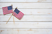 This is a close up photo of two American flags on and old retro white wooden table. This is a great image for memorial day, veterans Day, etc.