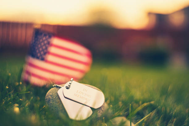 memorial day flag and dog tags in evening sunshine - memorial day стоковые фото и изображения
