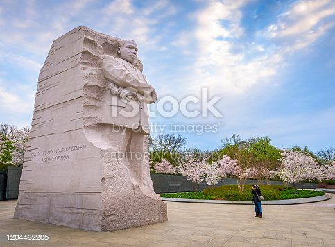 Washington DC, USA - April 12, 2015: A man photographs the Martin Luther King Jr. Memorial during spring season in West Potomac Park. The work was created by Lei Yixin and opened to the public August 22, 2011.