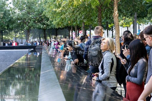 New York, United States of America - September 19, 2019: People standing at the north pool of the World Trade Center Ground Zero Memorial in Lower Manhattan.