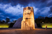Washington, United States - August 18, 2014: People meander about the Martin Luther King, Jr. Memorial in West Potomac Park, southwest of the National Mall, during the nighttime. The memorial honors civil rights leader Martin Luther King, Jr. (1929-1968) and was sculpted by Chinese sculptor Lei Yixin (born 1954).