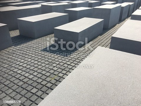 Berlin, Germany - July 13, 2018: The Memorial to the Murdered Jews of Europe, also known as the Holocaust Memorial (German: Holocaust-Mahnmal), consists of 2711 concrete slabs or stelae, arranged in a grid pattern on a sloping field. It is a memorial for the Jewish victims of the Holocaust, and was designed by architect Peter Eisenman and engineer Buro Happold. The memorial opened to the public in May 2005.