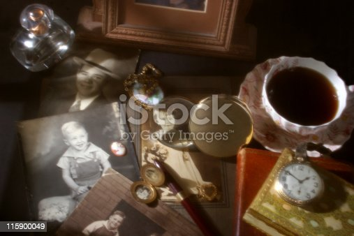 Collection of vintage photographs, one highlighted through a magnifying glass.  Cup of coffee, old pocket watch, locket, necklace, choaker locket, perfume bottle,  cameo and fountain pen.  Diffused, soft lighting creates the scene and atmosphere. Retro, old-fashioned.