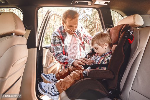 istock Memories made together last a lifetime. Father fastening his baby boy that sitting in a car in safety chair. Family road trip 1133373272