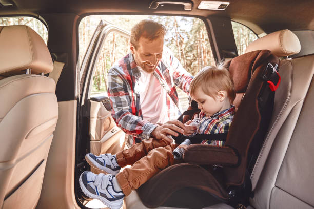 Memories made together last a lifetime. Father fastening his baby boy that sitting in a car in safety chair. Family road trip Father is adjusting child's car seat, while kid is playing with toy binoculars. Side view last stock pictures, royalty-free photos & images