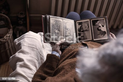 Woman looks at old photos of family members .