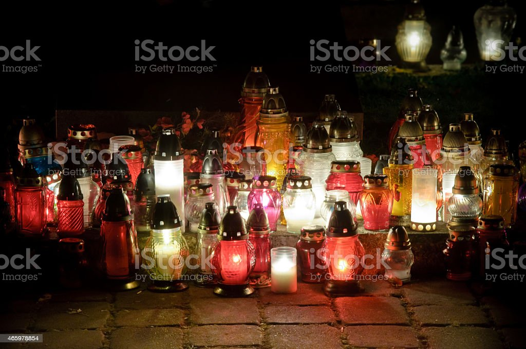 Memory candles on the graves of the night in the cemetery stock photo