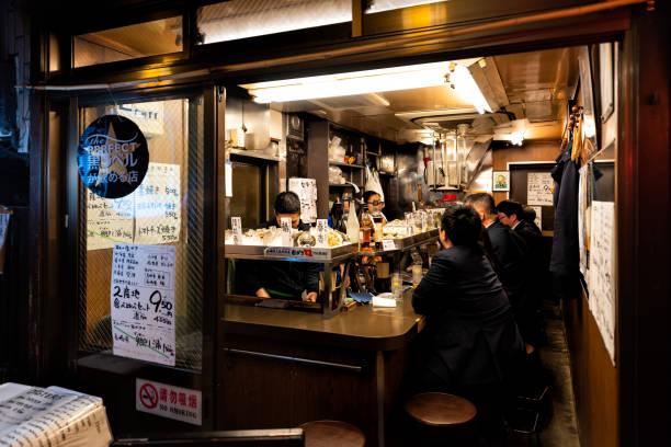 記憶小巷小巷與izakaya酒吧,人們坐在和吃在人行道上在東京市晚上,廚師做飯 - 吧 公共飲食地方 個照片及圖片檔
