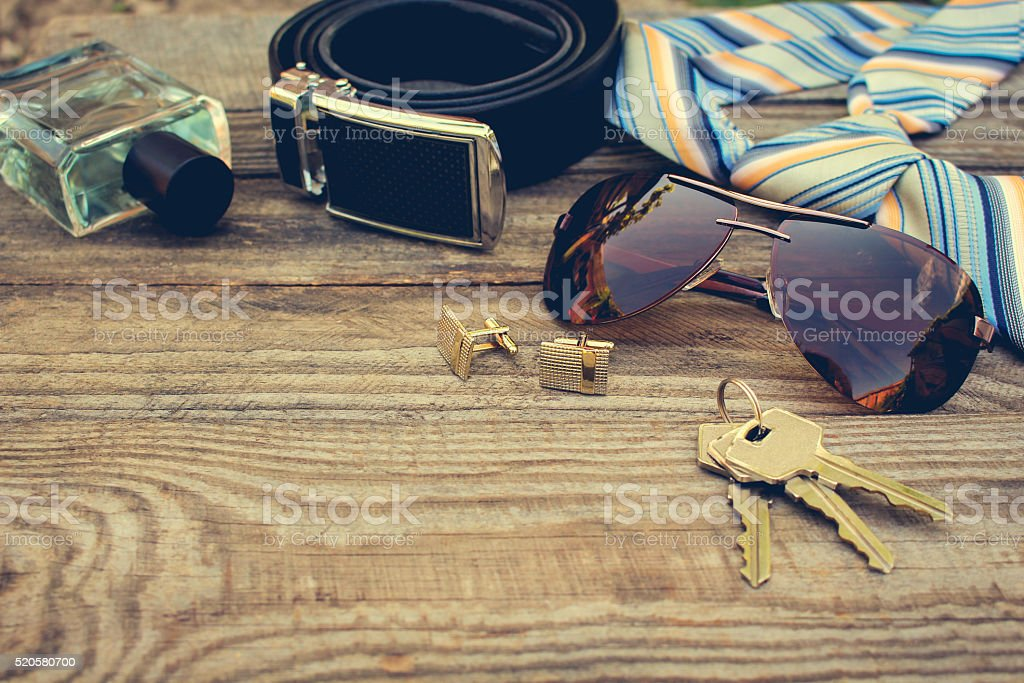 Men accessories: sunglasses, tie, cufflinks, strap, keys, perfume stock photo