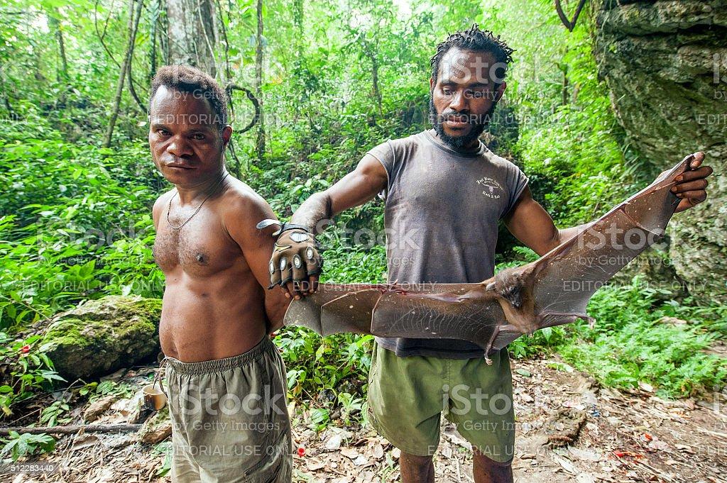 Men and a fruit bat stock photo