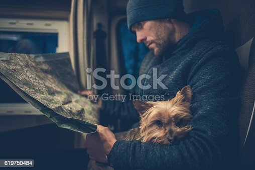 Men and His Dog Friend. Australian Silky Terrier York Relaxing on the Traveling Men Legs. Traveling Pet in the  Motorhome Camper.