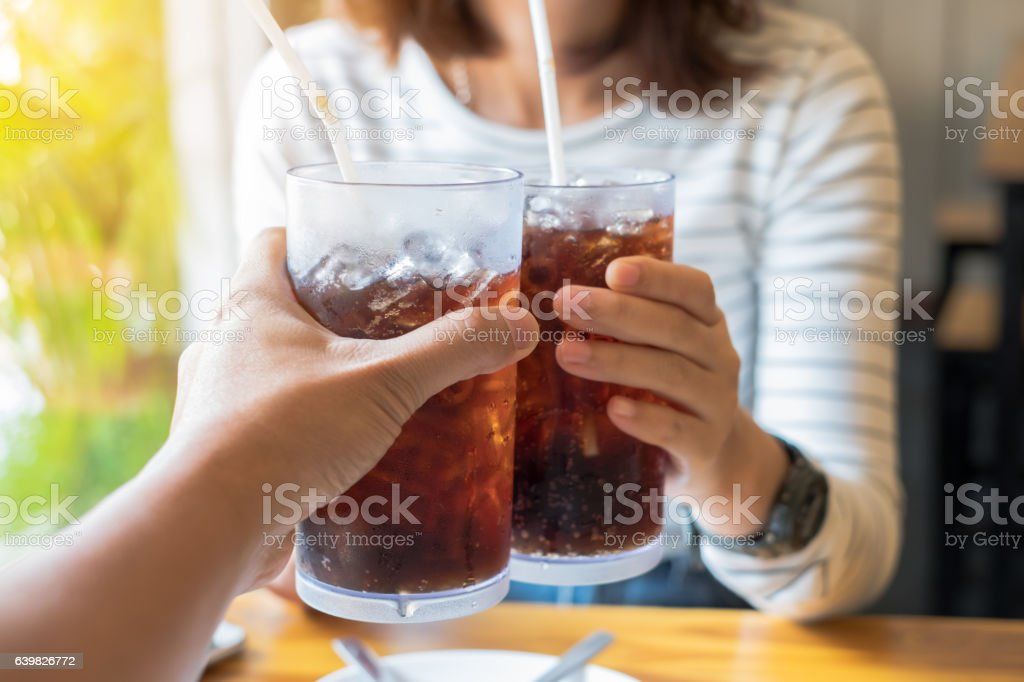 Men and Woman hand giving glass of cola stock photo