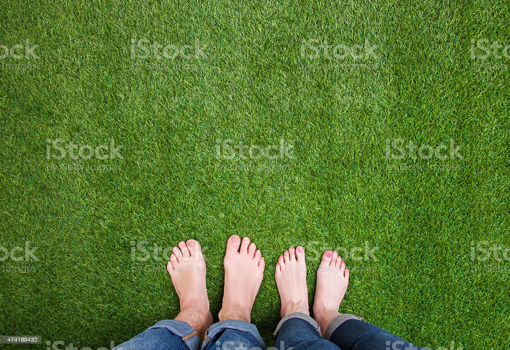 Men and woman  legs standing together on grass stock photo