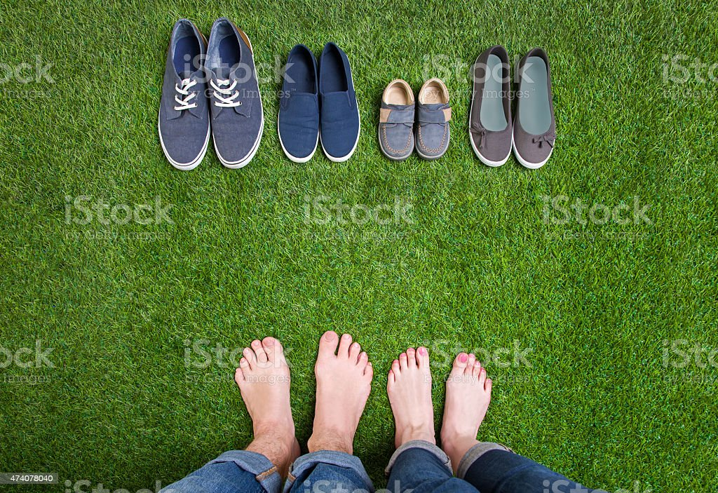 Men and woman legs with shoes standing  on grass stock photo
