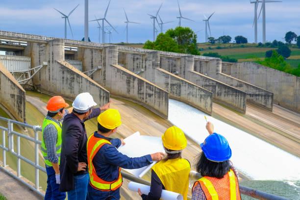 남자와 여자 엔지니어와 감독자 회의 건설 현장에서 청사진을 읽고 서. - 댐 뉴스 사진 이미지
